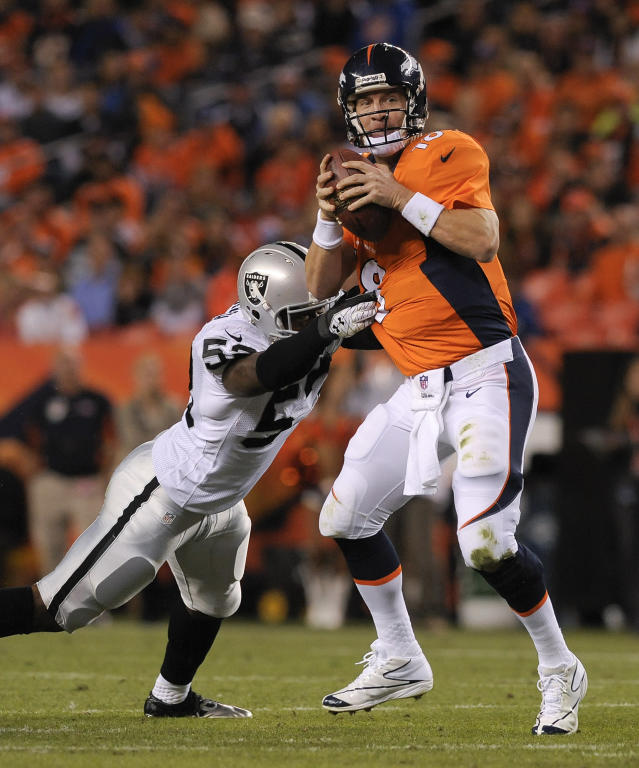 Denver Broncos quarterback Peyton Manning (18) scrambles away from Oakland Raiders middle linebacker Nick Roach (53) in the third quarter of an NFL football game, Monday, Sept. 23, 2013, in Denver. (AP Photo/Jack Dempsey)