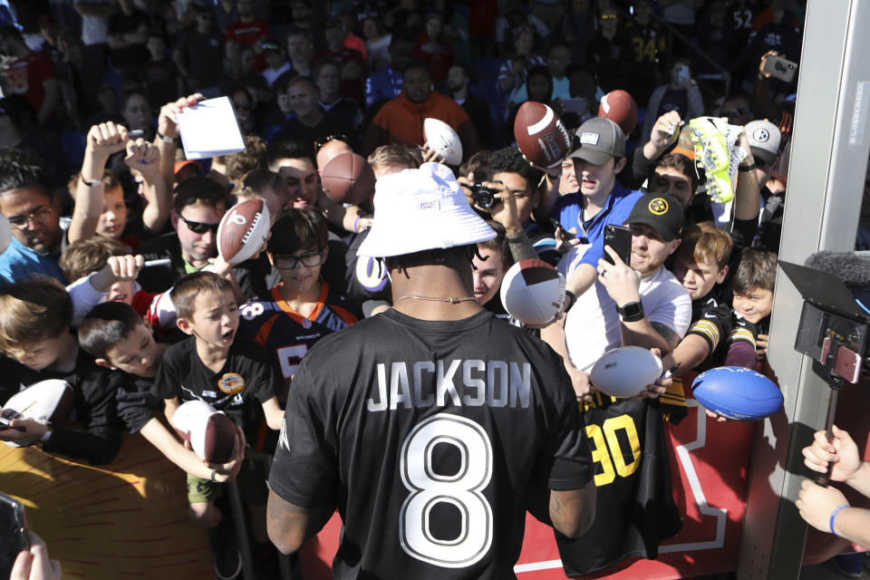"""FILE - In this Jan. 25, 2020, file photo, AFC quarterback Lamar Jackson of the Baltimore Ravens signs autographs for fans during Pro Bowl NFL football practice in Kissimmee, Fla. Lamar Jackson announced he will hold his annual """"Funday with LJ"""" event in Florida amid the state's spike in coronavirus cases. Jackson's third annual event will be held Saturday and Sunday in his hometown of Pompano Beach, Florida, according to a flyer shared on his Instagram page Monday, July 6, 2020. Social gatherings in groups of more than 10 people is currently not allowed in Pompano Beach, according to the city's website.(AP Photo/Gregory Payan, File)"""