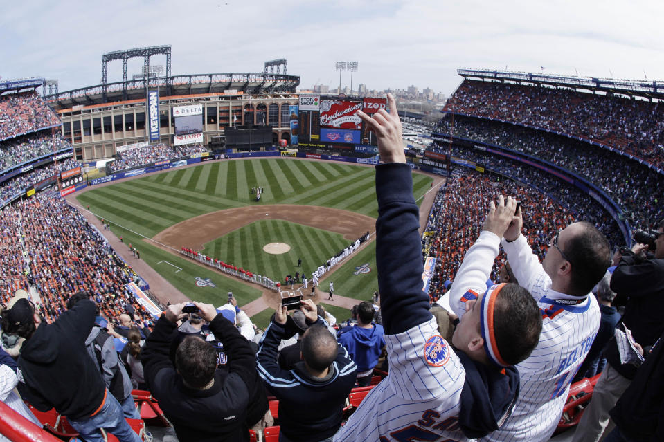 FILE - In this April 8, 2008, file photo, New York Mets fans look skyward for a fly-over at the end of the national anthem before an opening day baseball game against the Philadelphia Phillies at Shea Stadium in New York. To baseball fans, opening day is an annual rite of springthat evokes great anticipation and warm memories. This year's season was scheduled to begin Thursday, March 26, 2020, but there will be no games for a while because of the coronavirus outbreak. (AP Photo/Julie Jacobson, File)