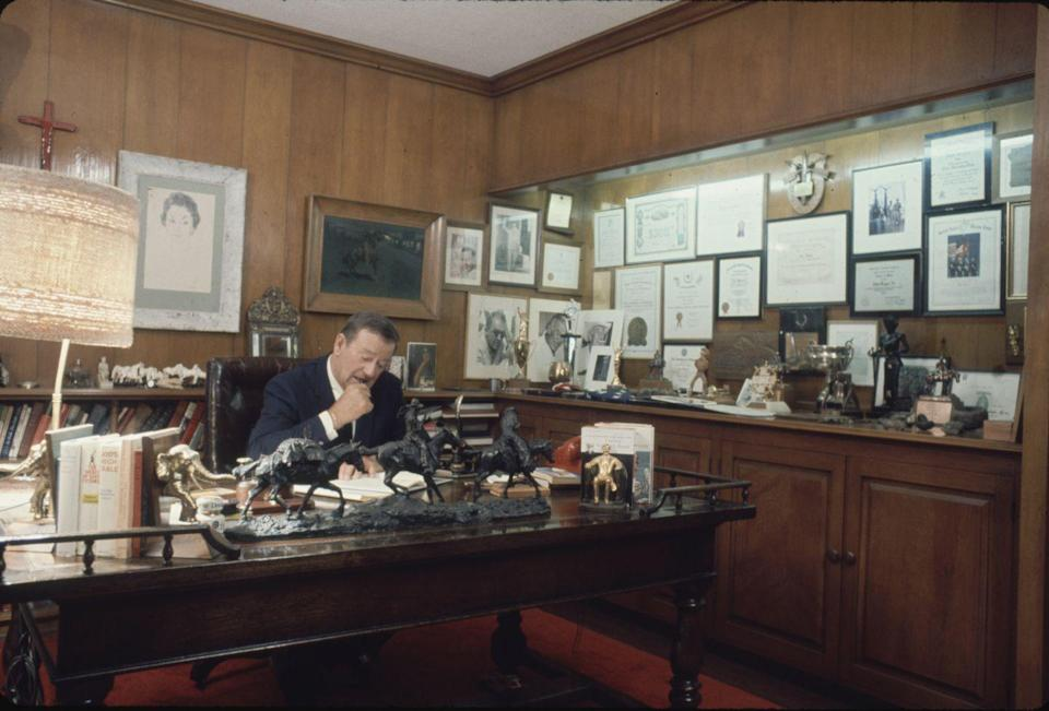 <p>John Wayne gets down to business in his home office in 1969. The famous actor's wood-paneled study makes room for the many accolades and memorabilia that covers his walls. </p>