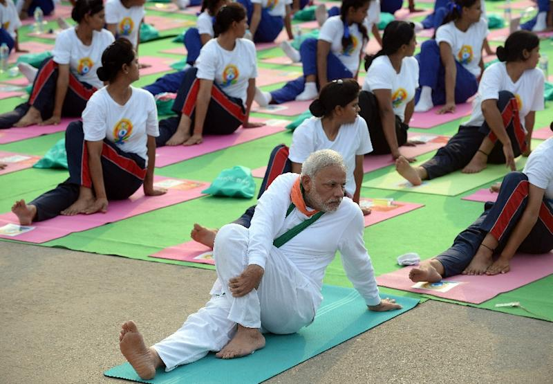 Indian Prime Minister Narendra Modi (C) participates in a mass yoga session along with other yoga practitioners to mark International Yoga Day on Rajpath Avenue in New Delhi on June 21, 2015