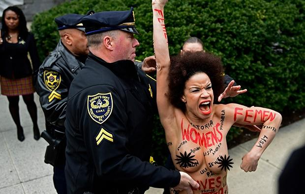Topless protester arrested at Bill Cosby trial.