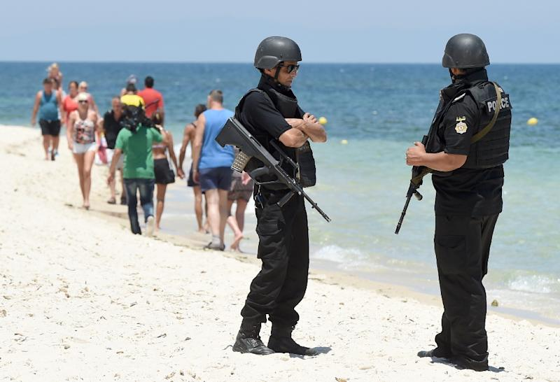 Tunisian police patrol the beach as tourists take part in a ceremony on July 3, 2015, in memory of those killed by a jihadist gunman in front of the Riu Imperial Marhaba Hotel in Port el Kantaoui (AFP Photo/Fethi Belaid)