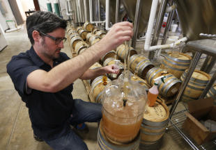 Co-Owner of Ardent Craft Ales, Kevin O'Leary, takes a sample of Persimmon beer at the facility in Richmond, VA., Tuesday, Dec. 2, 2014. Ardent Craft Ales is tapping into the Virginia Historical Society's collections to serve up a 300-year-old beer made with persimmons from a cookbook from the 1700s. The beer recipe is one of several in the society's collection that provide a glimpse into what Virginians and others were drinking in the 18th century. (AP Photo/Steve Helber)