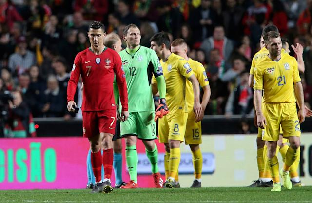 Portugal's Cristiano Ronaldo, left, walks with Ukraine goalkeeper Andriy Pyatov, third from left, at the end of the Euro 2020 group B qualifying soccer match between Portugal and Ukraine at the Luz stadium in Lisbon, Friday, March 22, 2019. (AP Photo/Armando Franca)
