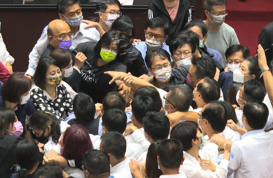 In this image taken from video by Taiwan's EBC, Premier Su Tseng-chang, in purple mask, tries to make a policy speech amid a scuffle between opposition Nationalist party and ruling Democratic Progressive Party lawmakersduring a parliament session in Taipei, Taiwan, Tuesday, Sept. 28, 2021. Taiwan's legislature on Tuesday descended into a rowdy brawl on Tuesday, after opposition lawmakers interrupted an important policy address and rushed the podium. (EBC via AP )