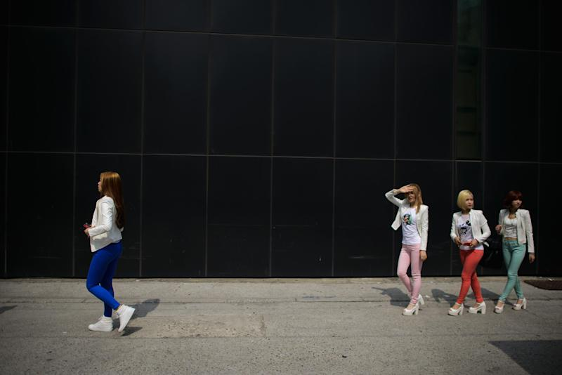 Members of the K-pop group 'Billion' walk to their car after visiting a stylist to prepare for a concert, in Seoul, June 10, 2014