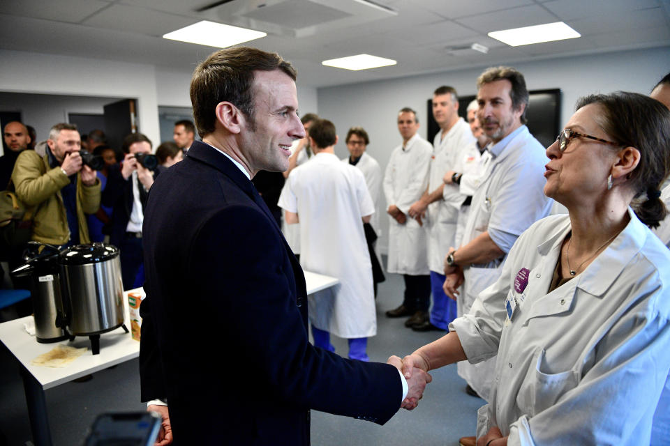 French President Emmanuel Macron shakes hands with medical staff as he visits the Pitie-Salpetriere hospital in Paris Thursday Feb. 27, 2020. As virus fears mount in France because of the outbreak in neighboring Italy, French President Emmanuel Macron is visiting a Paris hospital that has been in the forefront of testing and treating patients with the virus and where the latest virus patient died in France.( Martin Bureau, Pool via AP)