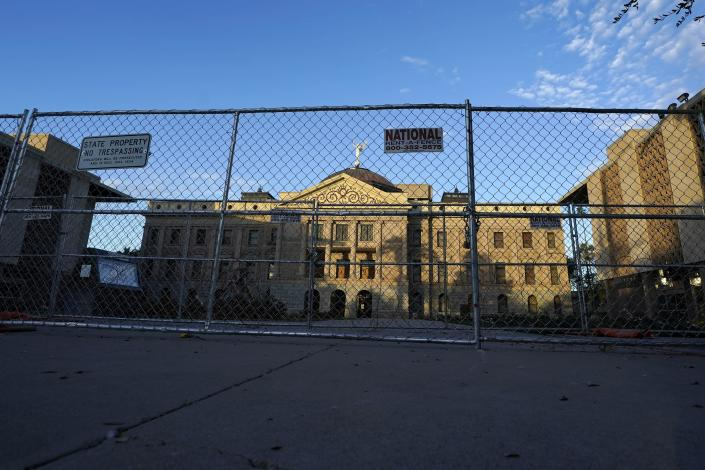 Two layers of security fencing is shown encircling the Arizona Capitol Saturday, Jan. 16, 2021, in Phoenix. With the FBI warning of potential violence at all state capitols Sunday, Jan. 17, the ornate halls of government and symbols of democracy looked more like heavily guarded U.S. embassies in war-torn countries. (AP Photo/Ross D. Franklin)