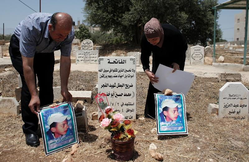 Father and mother of Palestinian teenager Mohammed Abu Khdeir pray at his grave in Shuafat, in Israel's annexed East Jerusalem, in July 2015 (AFP Photo/Ahmad Gharabli)