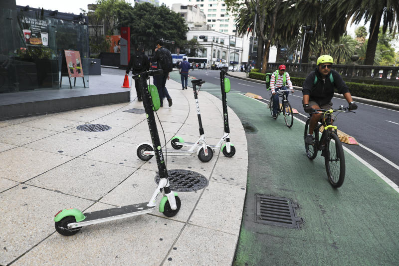 "Scooters are left after being used on the sidewalk on Reforma Avenue in Mexico City, Thursday, Aug. 1, 2019. An electric scooter firm has temporarily ceased operations in Mexico City because so many of its two-wheeled units have been stolen. The Grin company said in a statement that ""at present, the theft of our scooters in Mexico City is the biggest challenge."" (AP Photo/Eduardo Verdugo)"