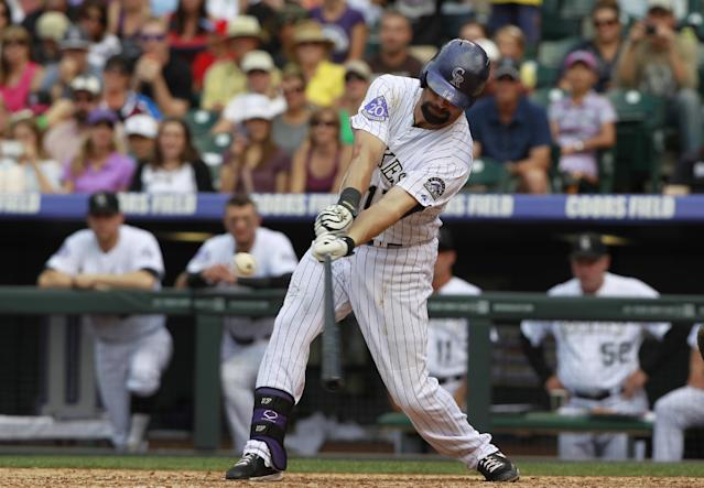 Colorado Rockies' Todd Helton connects on a double off Cincinnati Reds relief pitcher Curtis Partch in the seventh inning of a baseball game in Denver on Sunday, Sept. 1, 2013. The double was the 2,500th hit in Helton's career. (AP Photo/David Zalubowski)