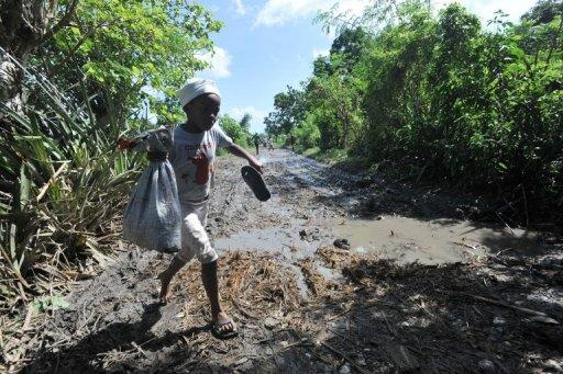 A child walks through damaged fields in Leogane, south of Port-au-Prince, one day after hurricane Sandy passed through