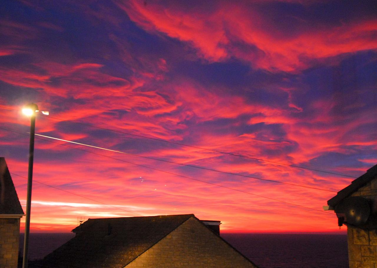 <p>The last embers of daylight create a fiery sunset over the sea in Portland, Dorset. (Rex) </p>