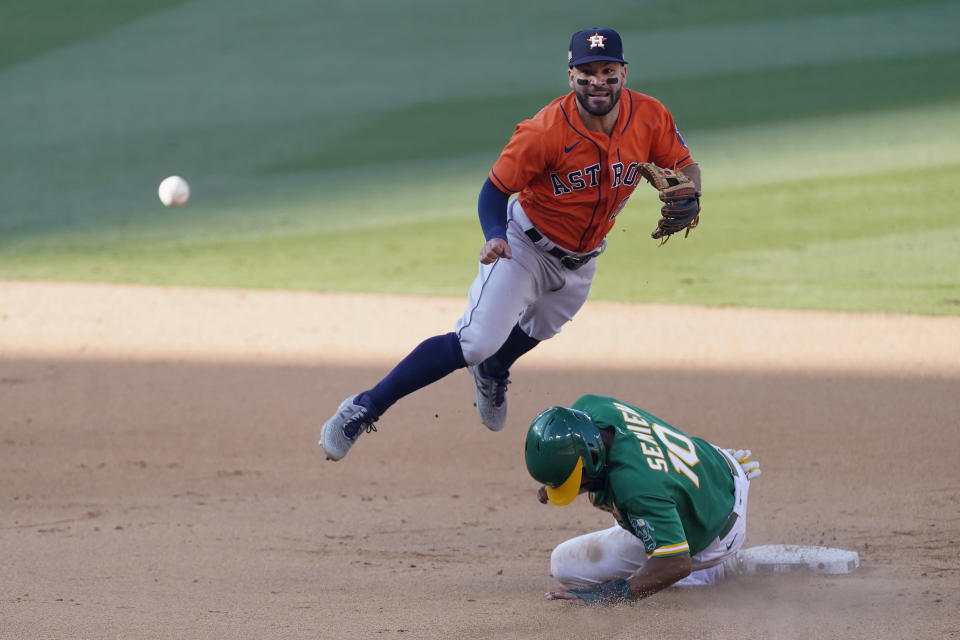 Houston Astros second baseman Jose Altuve, top, throws to first base after forcing out Oakland Athletics' Marcus Semien (10) at second base on a double play hit into by Chad Pinder during the ninth inning of Game 2 of a baseball American League Division Series in Los Angeles, Tuesday, Oct. 6, 2020. (AP Photo/Ashley Landis)