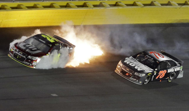 Smoke and flames come from Jeff Gordon's car after a collision with Martin Truex Jr. (78) during the NASCAR Sprint All-Star auto race at Charlotte Motor Speedway in Concord, N.C., Saturday, May 17, 2014. (AP Photo/Gerry Broome)