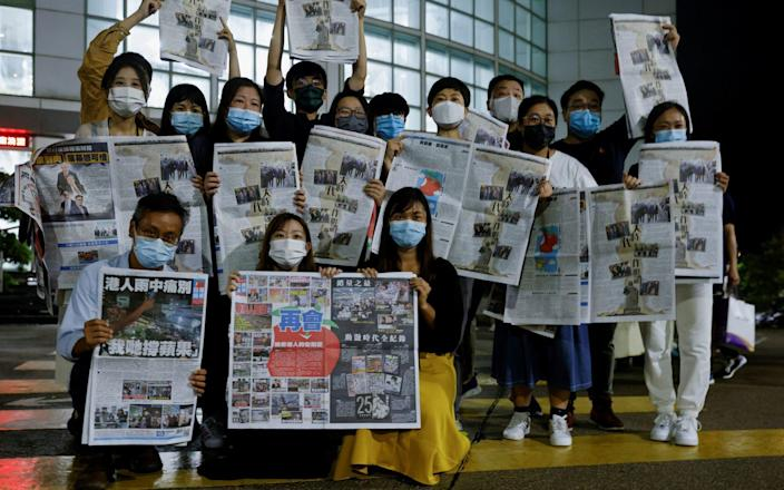 Staff outside Apple Daily's office with the final edition of the paper - REUTERS