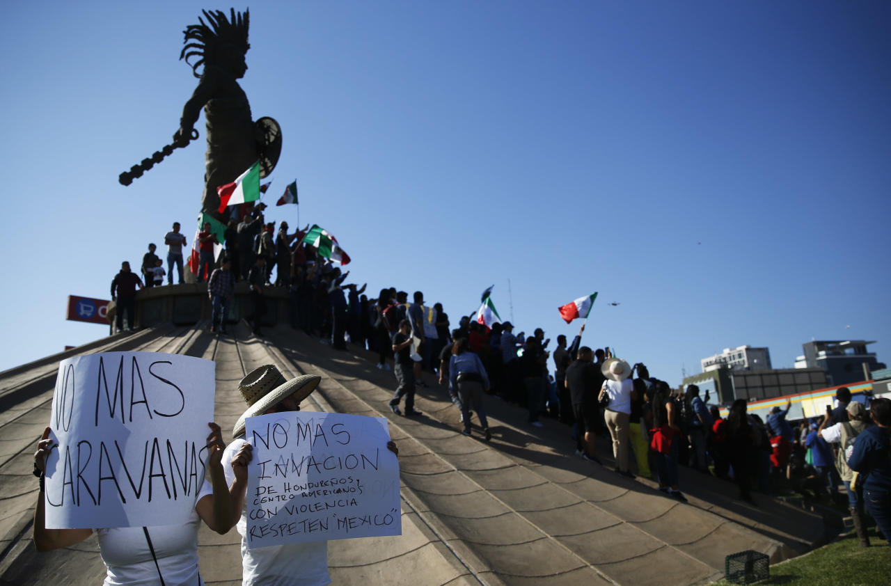 <p>Demonstrators stand under an statue of Aztec indigenous ruler Cuauhtemoc with Mexican flags to protest the presence of thousands of Central American migrants in Tijuana, Mexico, Nov. 18, 2018. (Photo: Marco Ugarte/AP) </p>