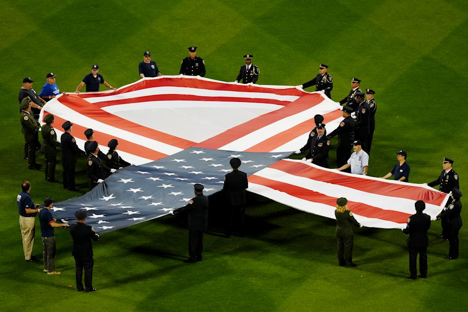 NEW YORK, NY - SEPTEMBER 11:  First responders are seen on the field holding an American Flag ribbon during the pre-game ceremony prior to the game between the New York Yankees and the New York Mets at Citi Field on Saturday, September 11, 2021 in New York, New York. (Photo by Daniel Shirey/MLB Photos via Getty Images)