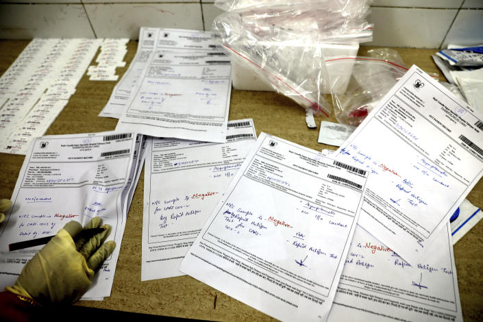 A health worker prepares the results of COVID-19 tests, most of which were found negative, at a hospital in New Delhi, India, Thursday, Feb. 11, 2021. When the coronavirus pandemic took hold in India, there were fears it would sink the fragile health system of the world's second-most populous country. Infections climbed dramatically for months and at one point India looked like it might overtake the United States as the country with the highest case toll. But infections began to plummet in September, and experts aren't sure why. (AP Photo/Manish Swarup)
