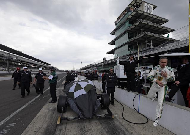 Driver Ed Carpente, right, jumps off the pit wall as rain halted activity on the first day of qualifications for Indianapolis 500 IndyCar auto race at the Indianapolis Motor Speedway in Indianapolis, Saturday, May 17, 2014. (AP Photo/Darron Cummings)