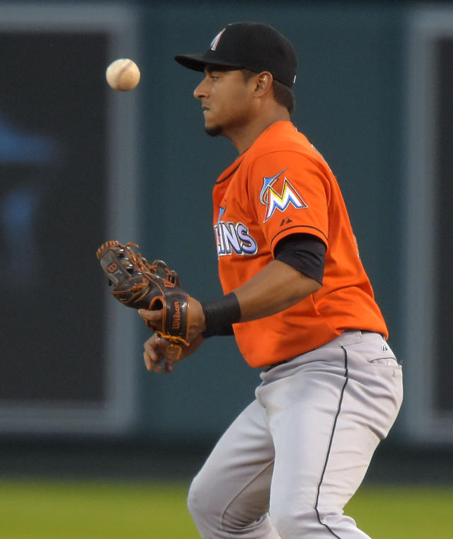 Miami Marlins second baseman Donovan Solano bobbles a ball hit by Los Angeles Angels' Kole Calhoun before throwing him out at first during the first inning of a baseball game, Wednesday, Aug. 27, 2014, in Anaheim, Calif. (AP Photo/Mark J. Terrill)