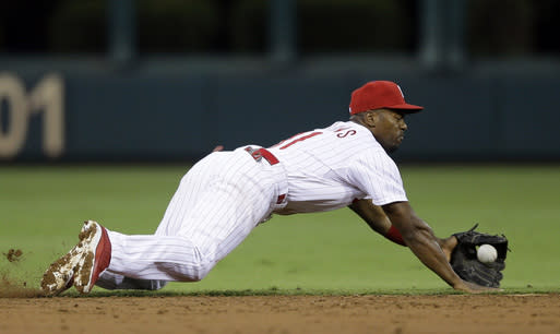Philadelphia Phillies shortstop Jimmy Rollins dives for a single by Chicago Cubs' Welington Castillo in the third inning of a baseball game, Tuesday, Aug. 6, 2013, in Philadelphia. (AP Photo/Matt Slocum)