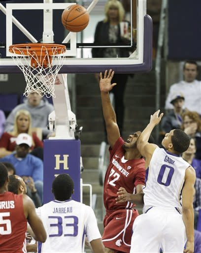 Washington State's Royce Woolridge (22) shoots as Washington's Abdul Gaddy (0) defends in the first half of an NCAA college basketball game on Sunday, March 3, 2013, in Seattle. (AP Photo/Ted S. Warren)