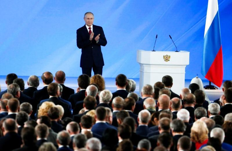 Russian President Vladimir Putin applauds after his speech to the State Council in Moscow