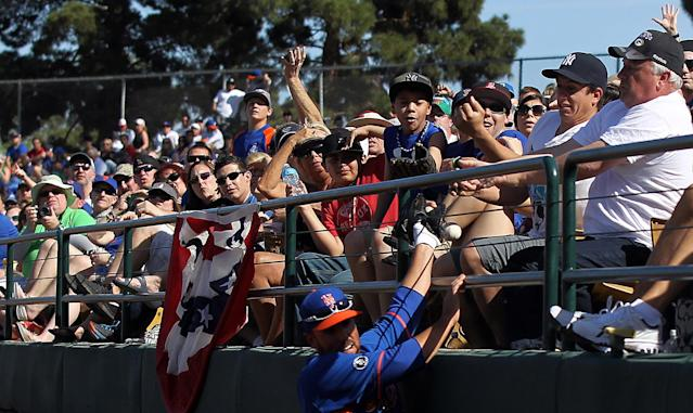 New York Mets first baseman Zach Lutz tries to catch a foul ball during a spring exhibition baseball game against the Chicago Cubs Sunday, March 16, 2014, in Las Vegas. (AP Photo/Isaac Brekken)