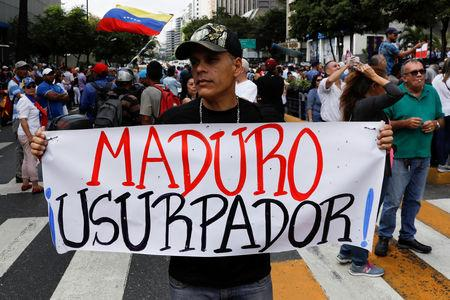 "A man holding a placard that reads ""Maduro usurper"" takes part in a gathering with members of the Venezuelan National Assembly in Caracas, Venezuela January 11, 2019. REUTERS/Manaure Quintero"