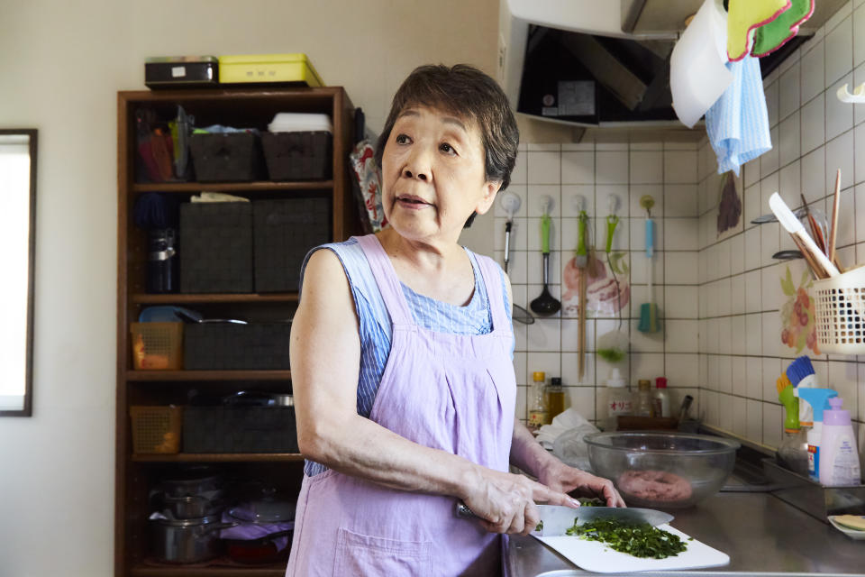 Asian senior woman cutting vegetables with a knife in the kitchen