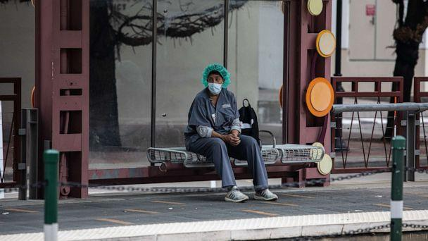 PHOTO: A health care worker waits at a bus stop after shift changes at Houston Methodist Hospital in Houston, July 12, 2020. (Erin Trieb/The New York Times/Redux Pictures)