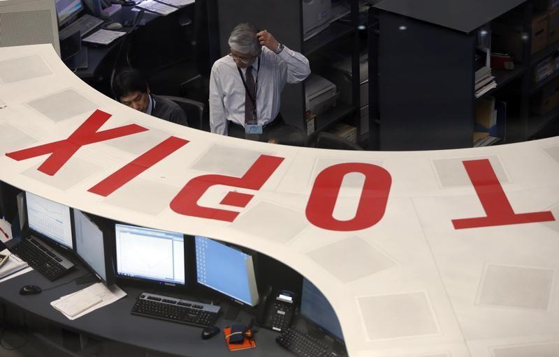 Employees of the Tokyo Stock Exchange (TSE) look at a monitor at the bourse at the TSE in Tokyo