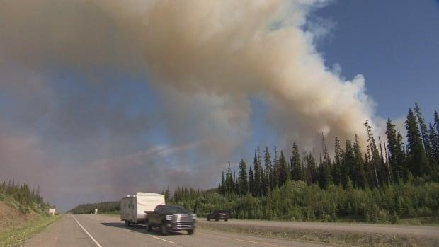 Traffic on Highway 97C passes a wildfire known as the Brenda Creek fire, 40 kilometres from West Kelowna, B.C., on Wednesday. (Radio-Canada - image credit)