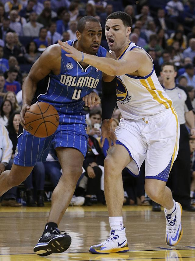 Orlando Magic guard Arron Afflalo, left, drives the ball against Golden State Warriors' Klay Thompson during the first half of an NBA basketball game Tuesday, March 18, 2014, in Oakland, Calif. (AP Photo/Ben Margot)