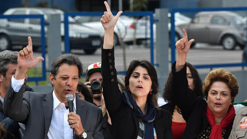 Brazil's presidential candidate for the Workers' Party (PT) Fernando Haddad (L) gestures next to vice presidential candidate Manuela D'Avila (C) and former president Dilma Rousseff after the official announcement of their candidacy outside the Federal Police Superintendence -where Lula da Silva is imprisoned- in Curitiba, in southern Brazil on September 11, 2018. - Haddad's ability to hold on to Lula's base will be key if he and his expected running mate, youthful communist Manuela d'Avila, are to reach the second round of Brazil's presidential election. (Photo by NELSON ALMEIDA / AFP)        (Photo credit should read NELSON ALMEIDA/AFP via Getty Images)
