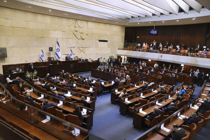 Israeli lawmakers attend the swearing-in ceremony for Israel's 24th government, at the Knesset, or parliament, in Jerusalem, Tuesday, April 6, 2021. The ceremony took place shortly after the country's president asked Prime Minister Benjamin Netanyahu to form a new majority coalition, a difficult task given the deep divisions in the fragmented parliament. (Alex Kolomoisky/Pool via AP)