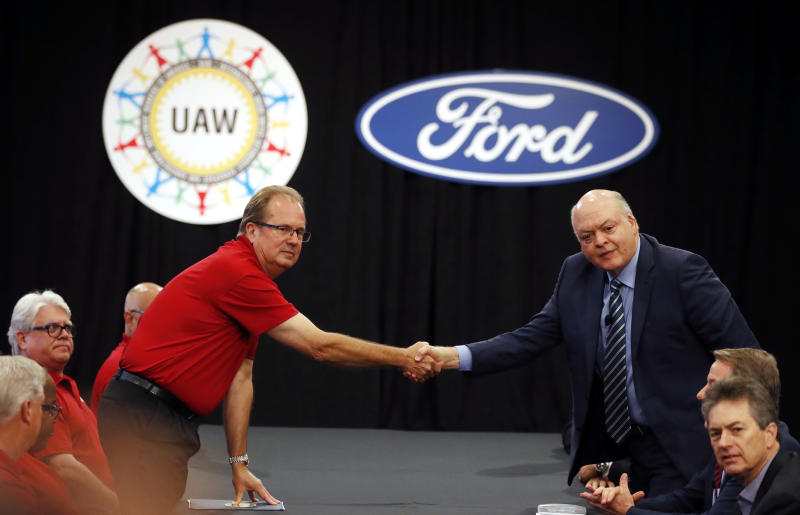 United Auto Workers President Gary Jones, left, and Ford Motor Co., Chief Executive Officer Jim Hackett shake hands to open their contract talks Monday, July 15, 2019, in Dearborn, Mich. (AP Photo/Carlos Osorio)