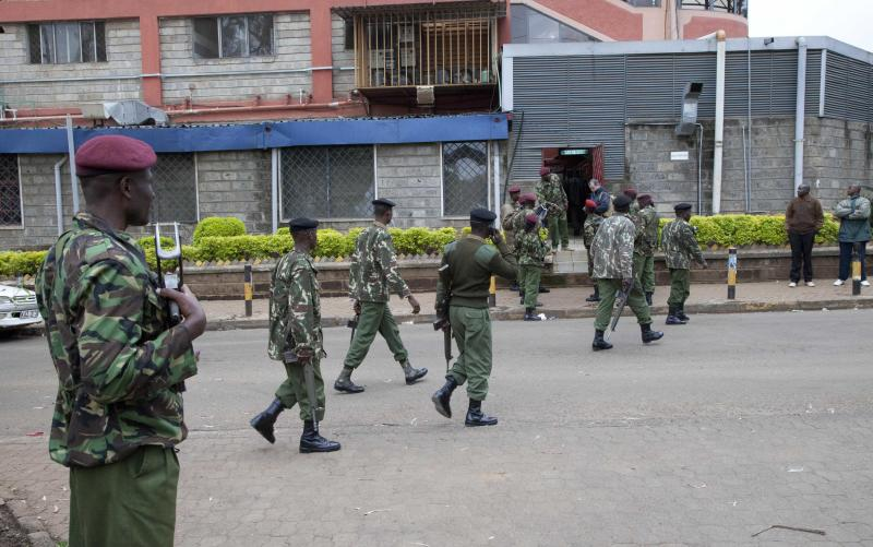 Kenya security personnel walk to their positions outside a shopping mall in Nairobi, Kenya, Sunday, Sept. 22, 2013. Kenya authorities said Islamic extremist attackers remain inside the upscale Kenyan shopping mall, holding an unknown number of hostages, after killing at least 39 and injuring 150 during the Saturday's attack. (AP Photo/Sayyid Azim)