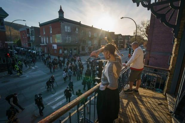 Residents look on from their balconies as protesters march through the streets of Montreal's Plateau-Mont-Royal borough.   (Radio-Canada/Ivanoh Demers - image credit)