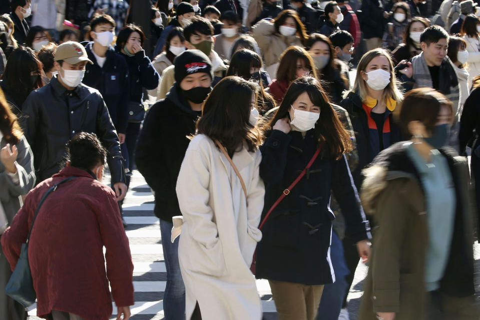 People wearing face masks to help curb the spread of the coronavirus walk around the scrambled intersection at the Shibuya shopping district in Tokyo Saturday, Dec. 26, 2020. Tokyo has confirmed 949 new cases of the coronavirus on Saturday, a record high for the Japanese capital, as the country struggles with an upsurge that is spreading nationwide. (Kyodo News via AP)
