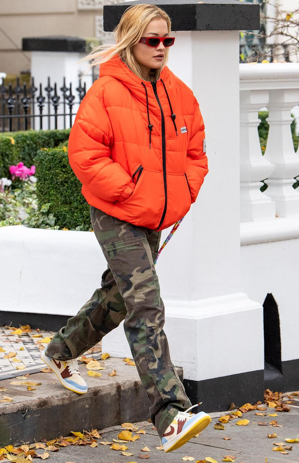 <p>Rita Ora wears a bright orange puffer coat and camo pants while leaving her home in London on Monday.</p>