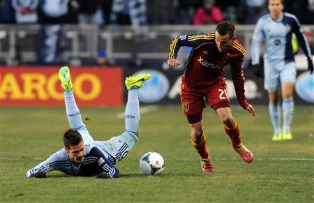 Dec 7, 2013; Kansas City, KS, USA; Sporting KC midfielder Benny Feilhaber (left) falls as he chases the ball with Real Salt Lake midfielder Luis Gil (21) in the second half of the 2013 MLS Cup at Sporting Park. Mandatory Credit: Denny Medley-USA TODAY Sports