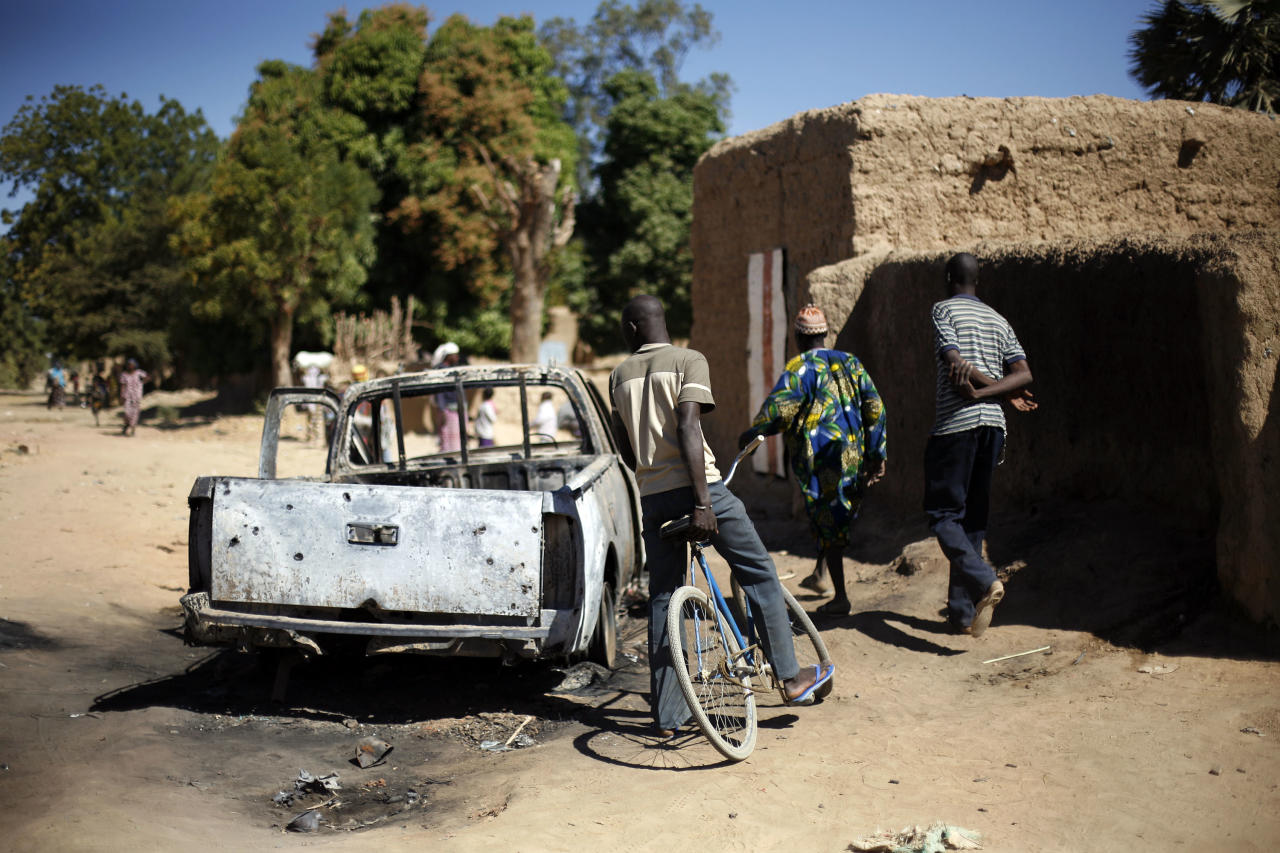 Residents walk past the charred remains of a truck used by radical Islamists on the outskirt of Diabaly, Mali, some 460kms (320 miles) north of the capital Bamako Monday Jan. 21, 2013. French and Malian troops were in the city whose capture by radical Islamists prompted the French military intervention. (AP Photo/Jerome Delay)