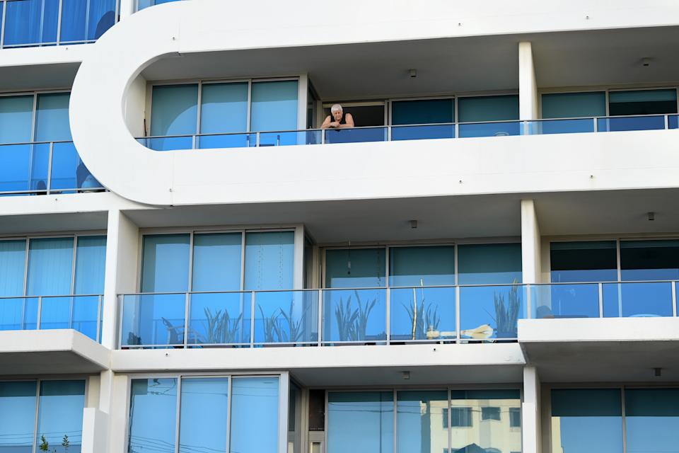 A man looks over his balcony towards an apartment (plants) where it is believed Queensland Police have established a crime scene in Labrador. Source: AAP