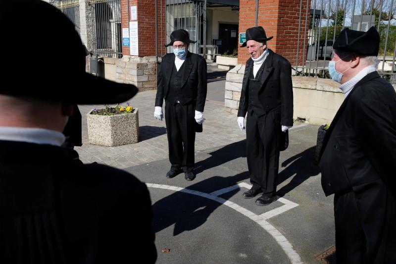 Members of the Charitable Brotherhood which first formed during the plague 800 years ago, talk in front of the cemetery after a burial ceremony in Bethune
