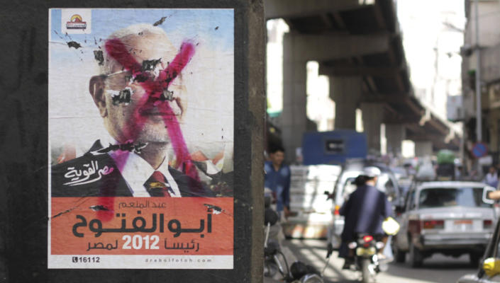 Egyptians pass by a defaced poster of a presidential candidate, Abdel-Moneim Abolfotoh in Cairo, Egypt, Monday, May, 21, 2012. The May 23-24 presidential election is the first since last year's ouster of longtime authoritarian ruler Hosni Mubarak. (AP Photo/Hasan Jamali)