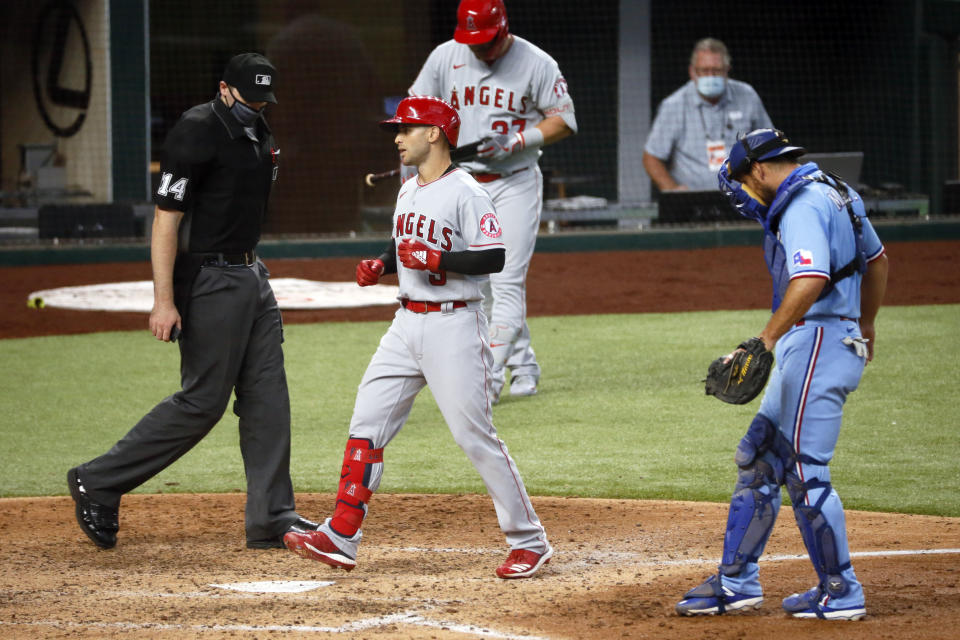Los Angeles Angels' Tommy La Stella, center, steps on home plate after hitting a two run home run as Texas Rangers catcher Jeff Mathis, right, and umpire Mark Wegner, left, look on during the fifth inning of a baseball game in Arlington, Texas, Sunday, Aug. 9, 2020. (AP Photo/Ray Carlin)