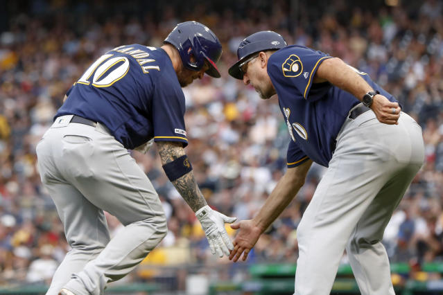 Milwaukee Brewers' Yasmani Grandal, left, is greeted by third base coach Ed Sedar as he rounds the bases after hitting a solo home run in the third inning of a baseball game against the Pittsburgh Pirates, Saturday, July 6, 2019, in Pittsburgh. (AP Photo/Keith Srakocic)